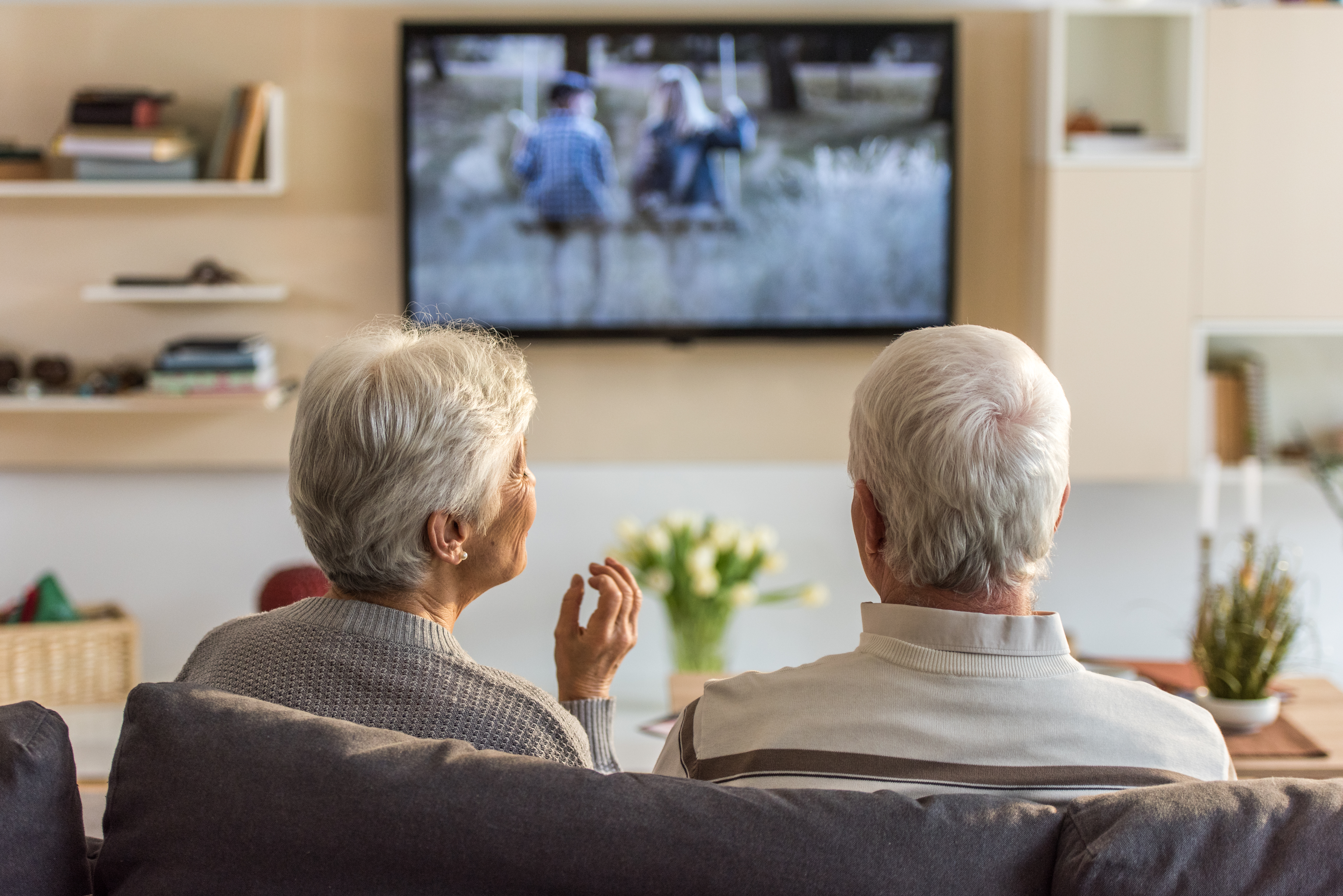 Senior couple sitting on sofa and watching television show at home.